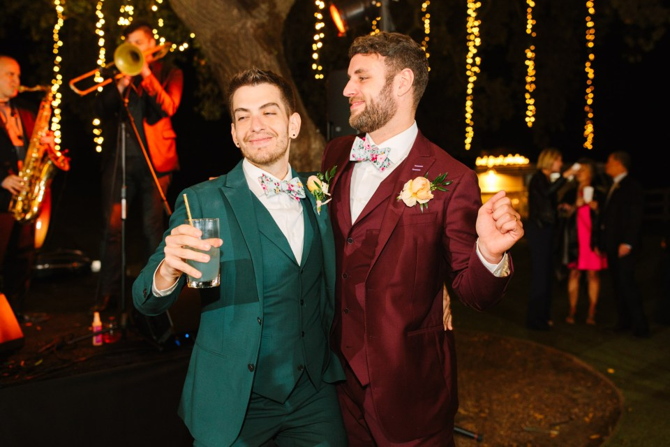 Grooms enjoying their wedding reception by Mary Costa Photography