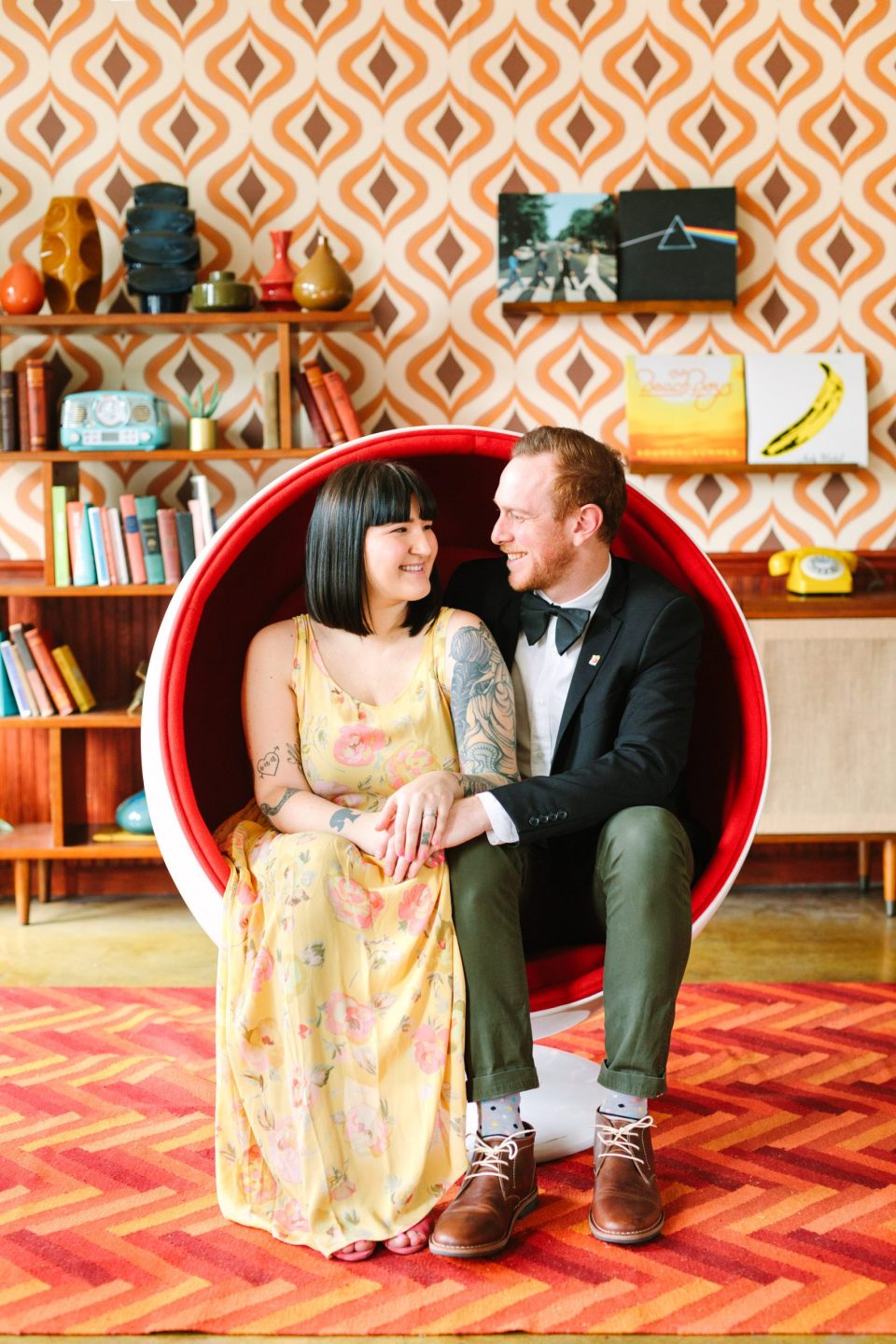 Couple in round chair surrounded by retro decor www.marycostaweddings.com