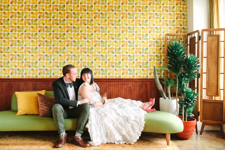 CouCouple on Mid Century Modern couch in retro room www.marycostaweddings.com