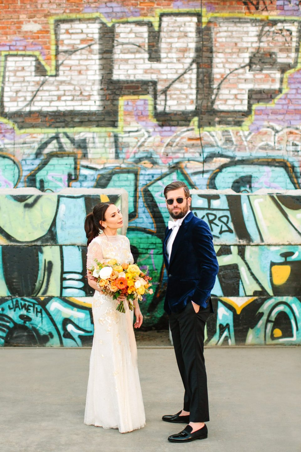 Bride and groom first look with graffiti backdrop www.marycostaweddings.com