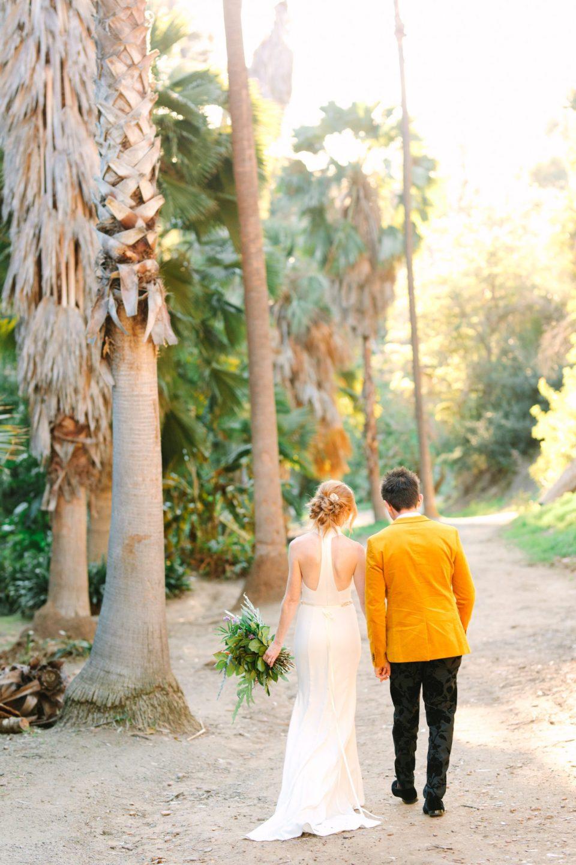 Bride and groom walking among palm trees - www.marycostaweddings.com