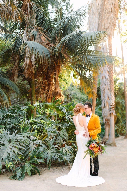 Couple embracing in palm garden - www.marycostaweddings.com