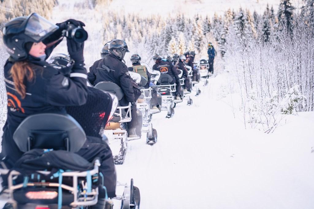 Skotersafari med bloggare, alla kör i ett led efter varandra i vintervitt landskap