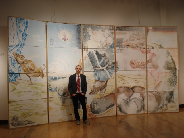 """Ian Warner with his piece """"Saga,"""" November 25, 2014, Memorial Union Gallery, NDSU. """"Saga"""" is a blend of Norse mythology with the culture of North Dakota."""
