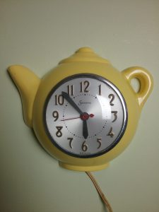 Yellow teapot-shaped electric wall clock by The Sessions Clock Company, 2018.