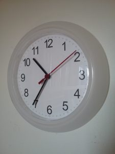 Round white wall clock with black numbers, black hands, and a red second hand, 2018.