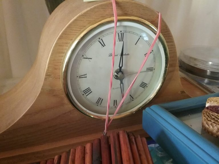 Wood mantle clock with 2 red rubber bands around it, 2018.