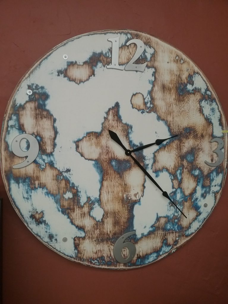 White clock with mottled brown and blue shapes that look like continents, 2018.