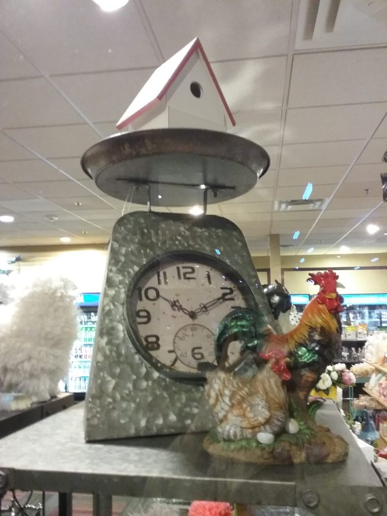 Clock in a scale with a birdhouse on top, 2019.