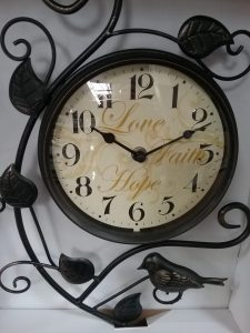 Love, Faith, Hope wall clock with a cream-colored face, black numbers and hands, and a black frame featuring leaves and a bird, 2018.