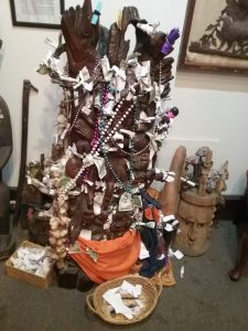 Altar with wishes written on pieces of paper wrapped with money at the New Orleans Historic Voodoo Museum, Dumaine Street, New Orleans, Louisiana, August 2019. This museum is privately operated and has three small rooms featuring quite a number of altars with offerings, along with the history of Voodoo Queen Marie Laveau and explanations of various aspects of Voodoo. Not far from the museum, there is a shop called Marie Laveau's on Bourbon Street (which is as rowdy as its reputation in the business district closer to Canal Street). We stopped in to Marie Laveau's, where there was an altar to her. I purchased a pack of tarot cards there, which seems an appropriate souvenir of New Orleans. This altar (the one pictured above) is perhaps the most inspirational thing I saw on my trip in terms of leading me to new ideas. I can't stop thinking about it.