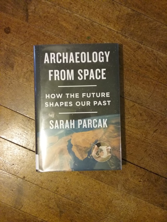 """""""Archaeology from Space: How the Future Shapes Our Past,"""" By Sarah Parcak. Normally, I would have cropped this picture so the book would have taken up most of the frame. Because I'm talking about space in this post, I wanted to give the impression of looking down on the book from on high. Mary Warner, 2019."""