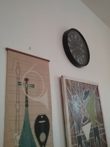 Black clock with two pieces of art showing musical scenes, 2019.