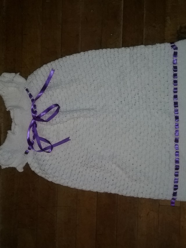 Daughter's crocheted white baptism gown with purple ribbon around the chest and two stripes of purple ribbon around the hem. Made by Mary Warner.