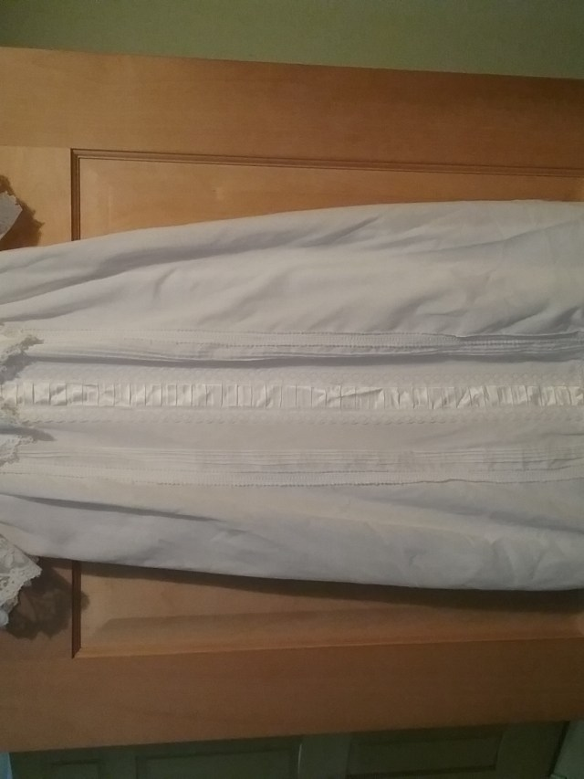 Young Son Number Two's baptism gown made of white cotton fabric and multiple types of white lace. Photo shows gown hanging on a door, with the length of the gown stretching half-to-two-thirds of the way down the door. Gown made by Mary Warner.