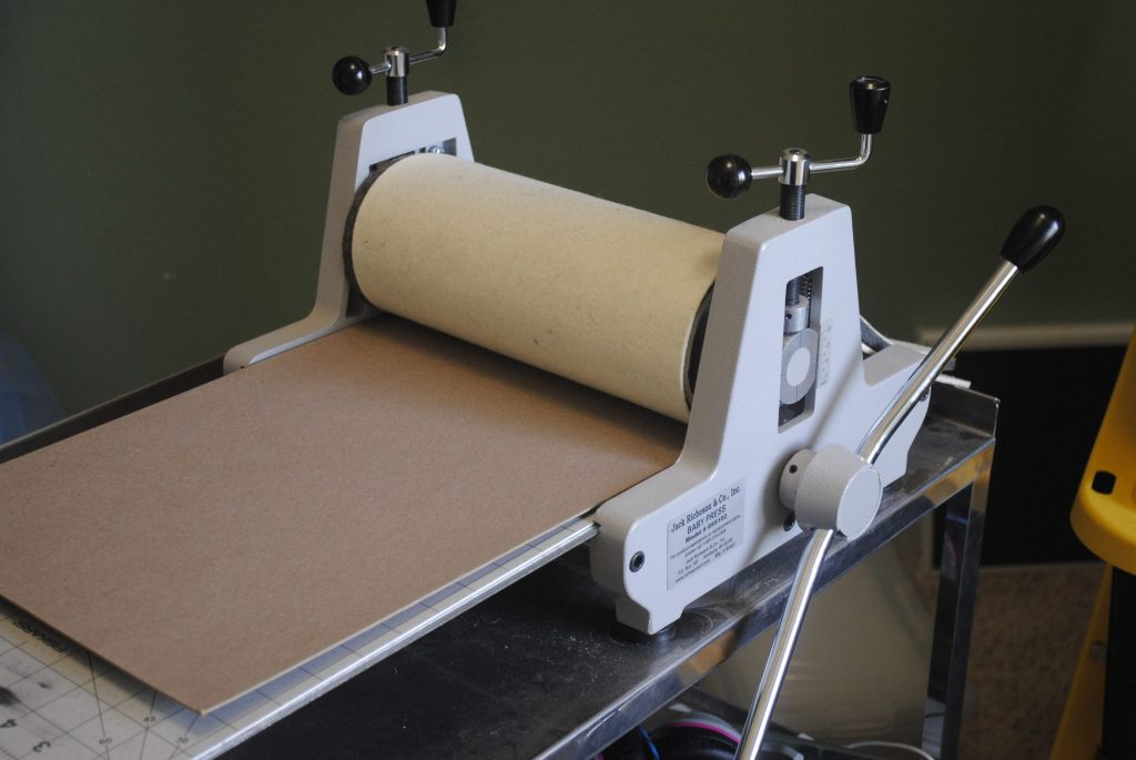 Place chipboard onto the etchng press