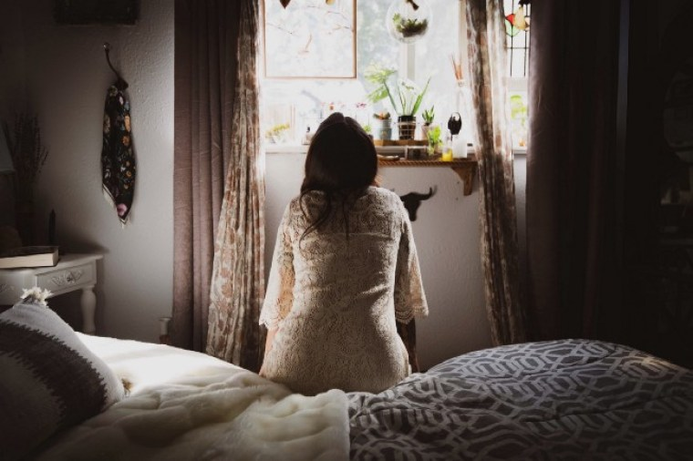 Woman sitting on edge of bed, looking towards window, trying to decide how to get up and move forward.
