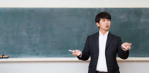 黒板の前に立って話をする教師