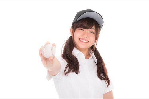 野球ボールを右手に持って前方に突き出す笑顔の女の子