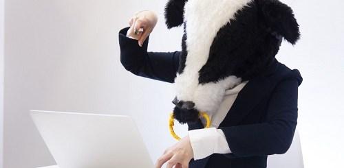 ノートパソコンを扱う牛の格好をした人