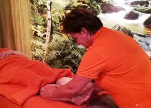 Karin tijdens het geven van een behandeling beenmassage
