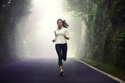 Woman running on road. Female runner jogging on mountain road tr