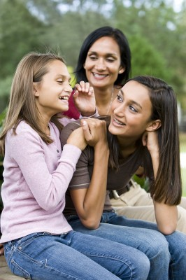 Affectionate Indian mother and two beautiful mixed-race daughters laughing together