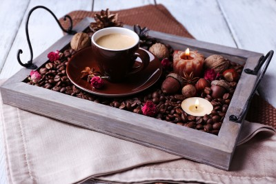Candles on vintage tray with coffee grains and spices, cup of te