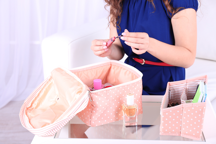 Girl applying make up on home interior background