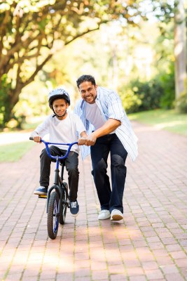 happy indian father teaching his son to ride a bicycle at the park