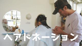 髪の毛を切っている少女の後姿と帽子を被った男性