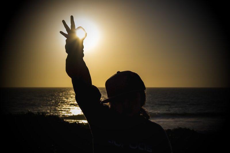 OKをしている人の手の中に太陽の光