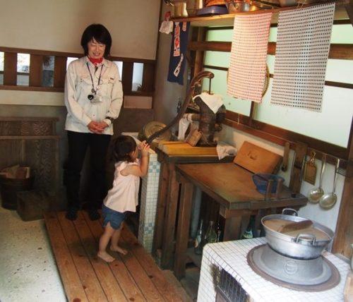 モリコロパークサツキとメイの家の台所に立つ女性と水くみをするこども