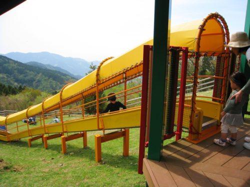 モーモーキッズランドの黄色い滑り台と滑る人