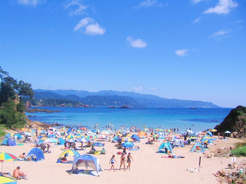青い空と海、砂浜に海水浴客が多くいる