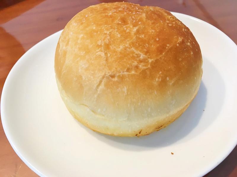 丸いきつね色のパンが白い皿に乗っている