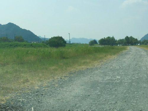 うしづま水辺の楽校まで砂利道が続いている、左に芝生