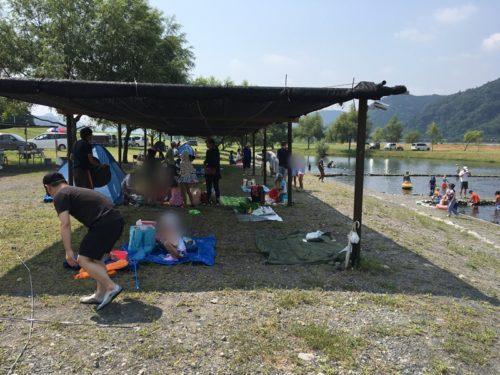 うしづま水辺の楽校の屋根のついた休憩所で涼む人々