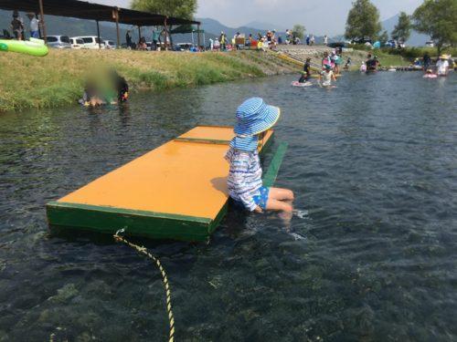 うしづま水辺の楽校のオレンジのイカダに座る子供