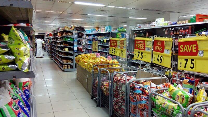 カートに商品が入り、上に値段が貼ってあるスーパーマーケットの中