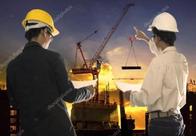 Two civil engineer working in building construction site against