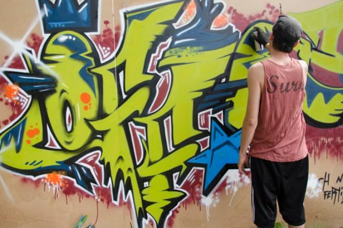 Orang yang sedang membuat gambar grafiti