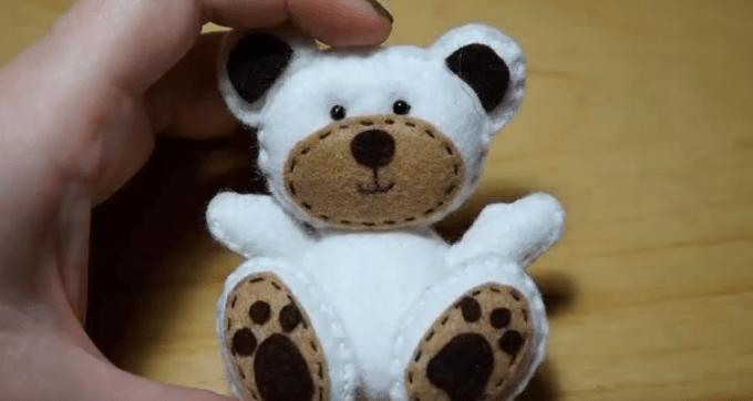 Menempelkan bagian kaki boneka ke badan saat membuat boneka dari kain flanel