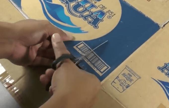 Menggunting kerdus untuk membuat tempat pensil dari koran bekas