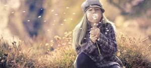 Flicka som sitter på en äng och blåser på en maskros