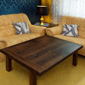 Soffbord i svart ek i vardagsrum med gula soffor