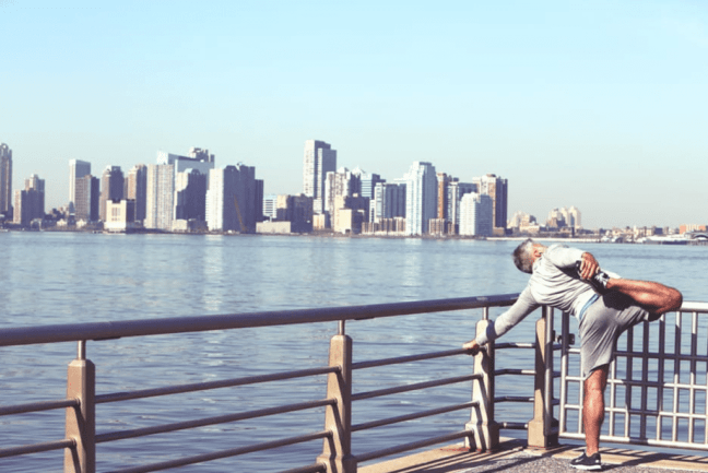 man stretching, preparing for a run overlooking cityscape