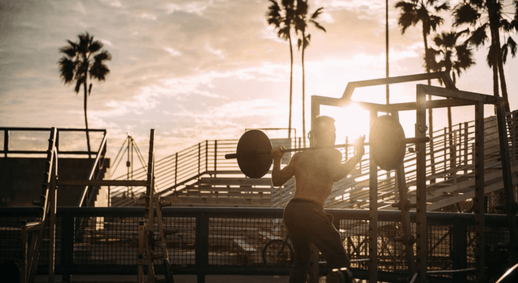 designing a strength training program - man squatting at an outdoor gym with a sunset in the background