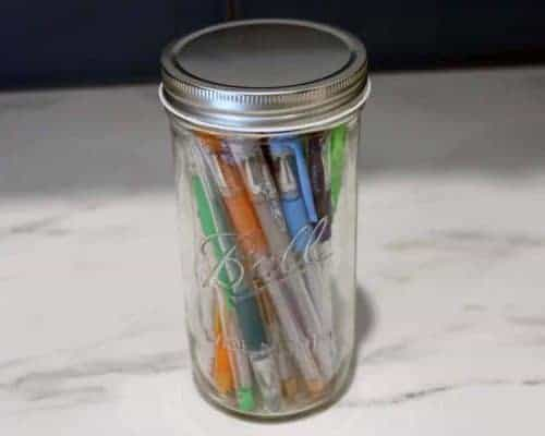 Wide mouth shiny silver storage lid on Pint & Half Ball Mason jar with pens