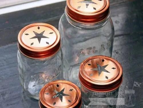 Copper star cutout lids and bands on 4 Ball Mason jars - a 4oz jelly jar, half pint jar, pint jar, and quart jar. Top view.